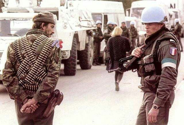 Serb and French soldier checking up eachother. Serb not impressed. Bosnia, 1992.